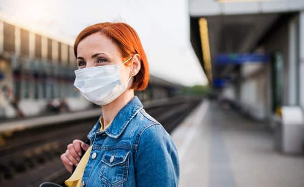 woman in mask waiting for train